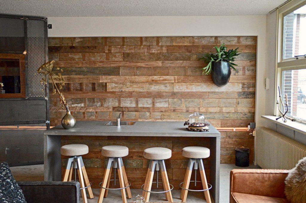 Des panneaux muraux en teck recyclé agrémentent ce mur. © Wall'In
