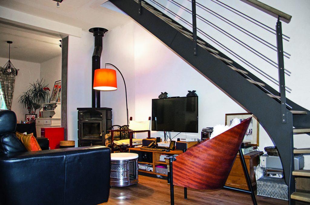 Salon à la déco familiale et escalier en métal